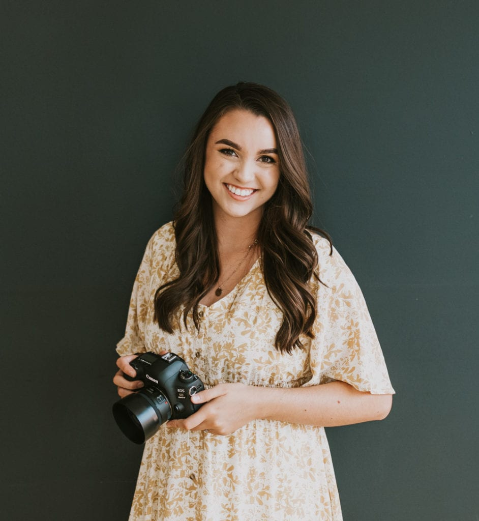 A girl holding a camera and smiling.