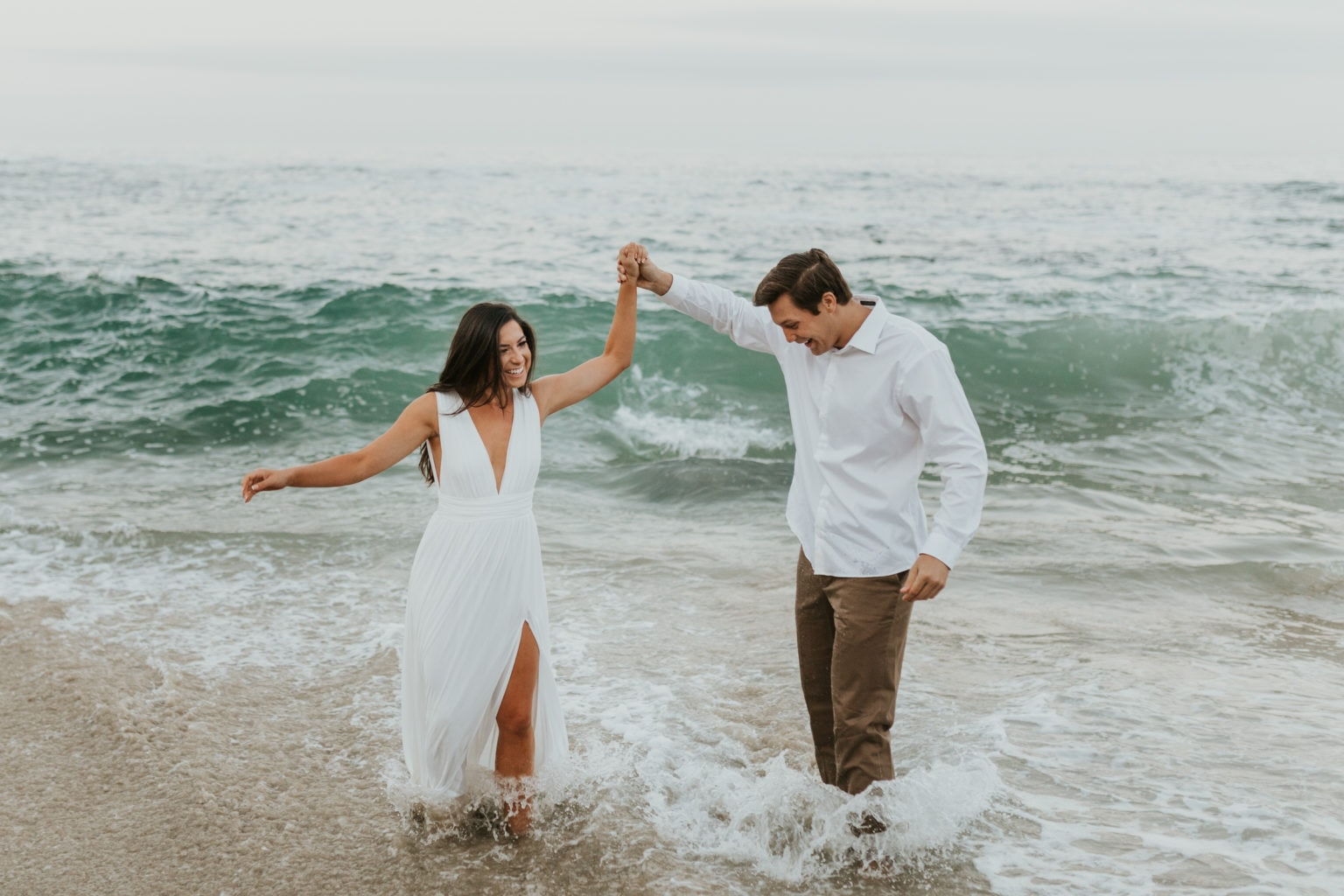 A bride and groom playing in the water on their elopement day.