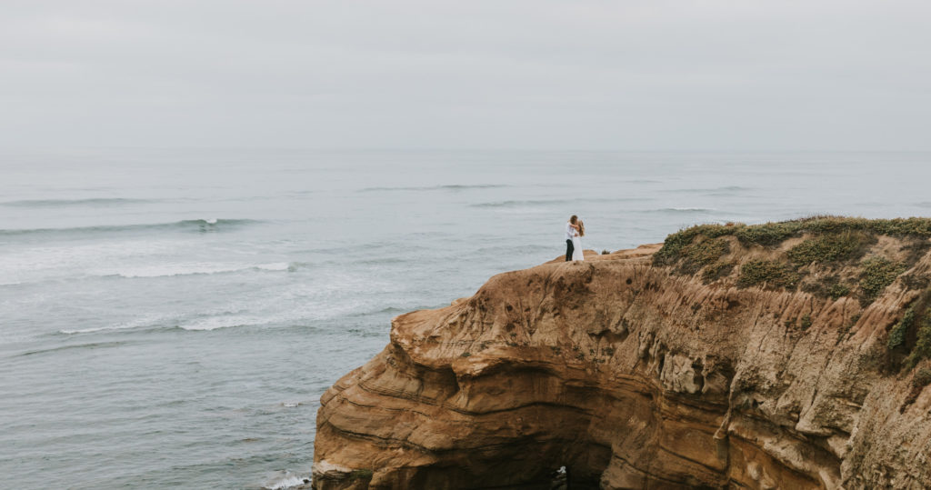 A bride and groom kissing on a cliff by the beach during their elopement.