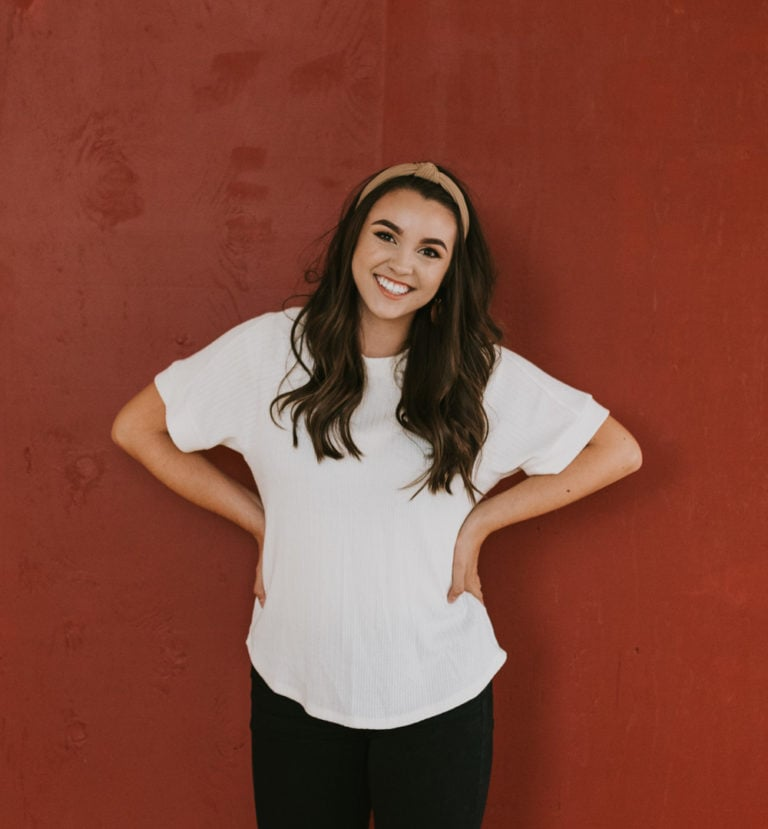 A girl smiling at the camera and standing against a red wall.