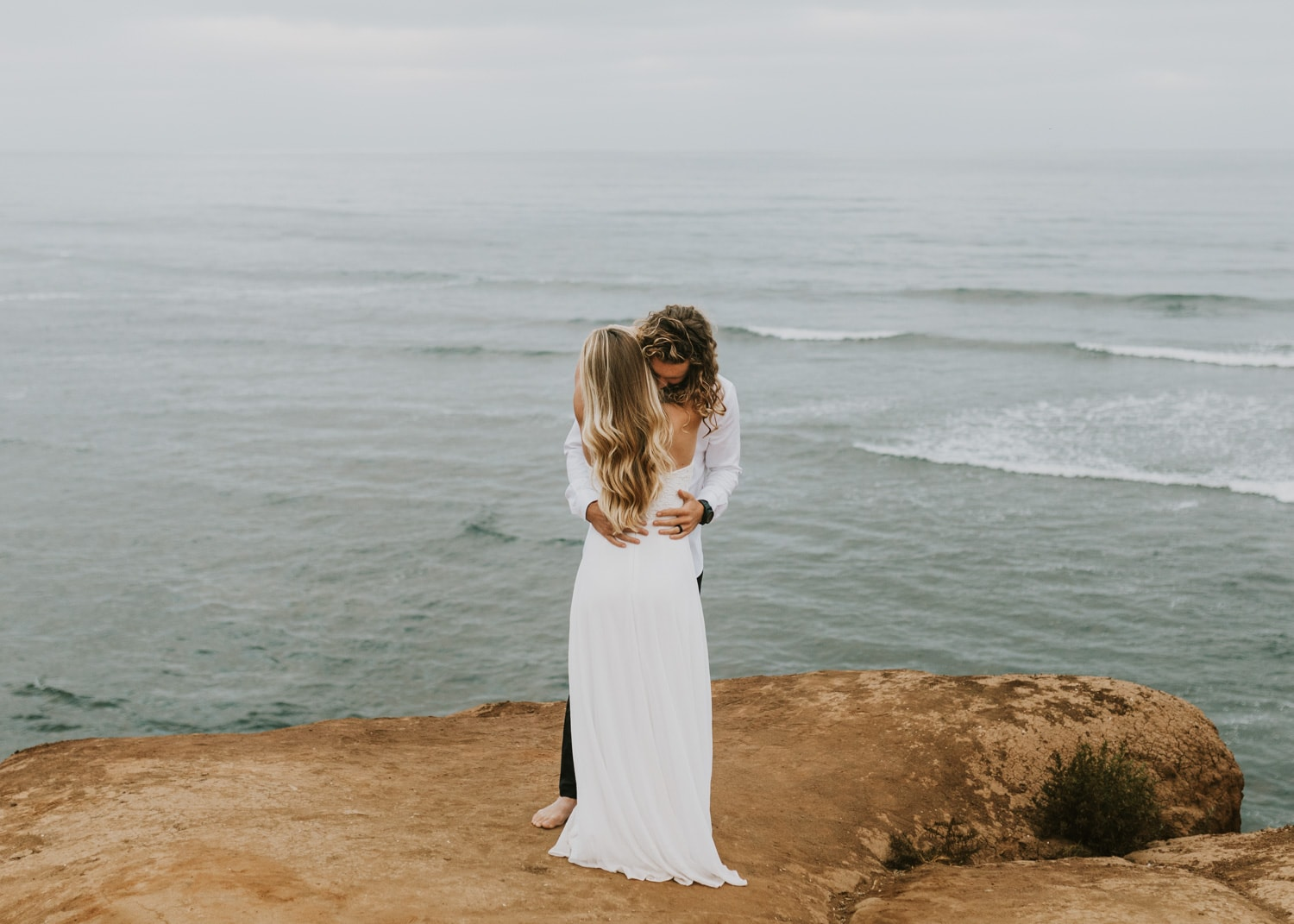 A bride and groom hugging at Sunset Cliffs for their Sunset Cliffs San Diego wedding.