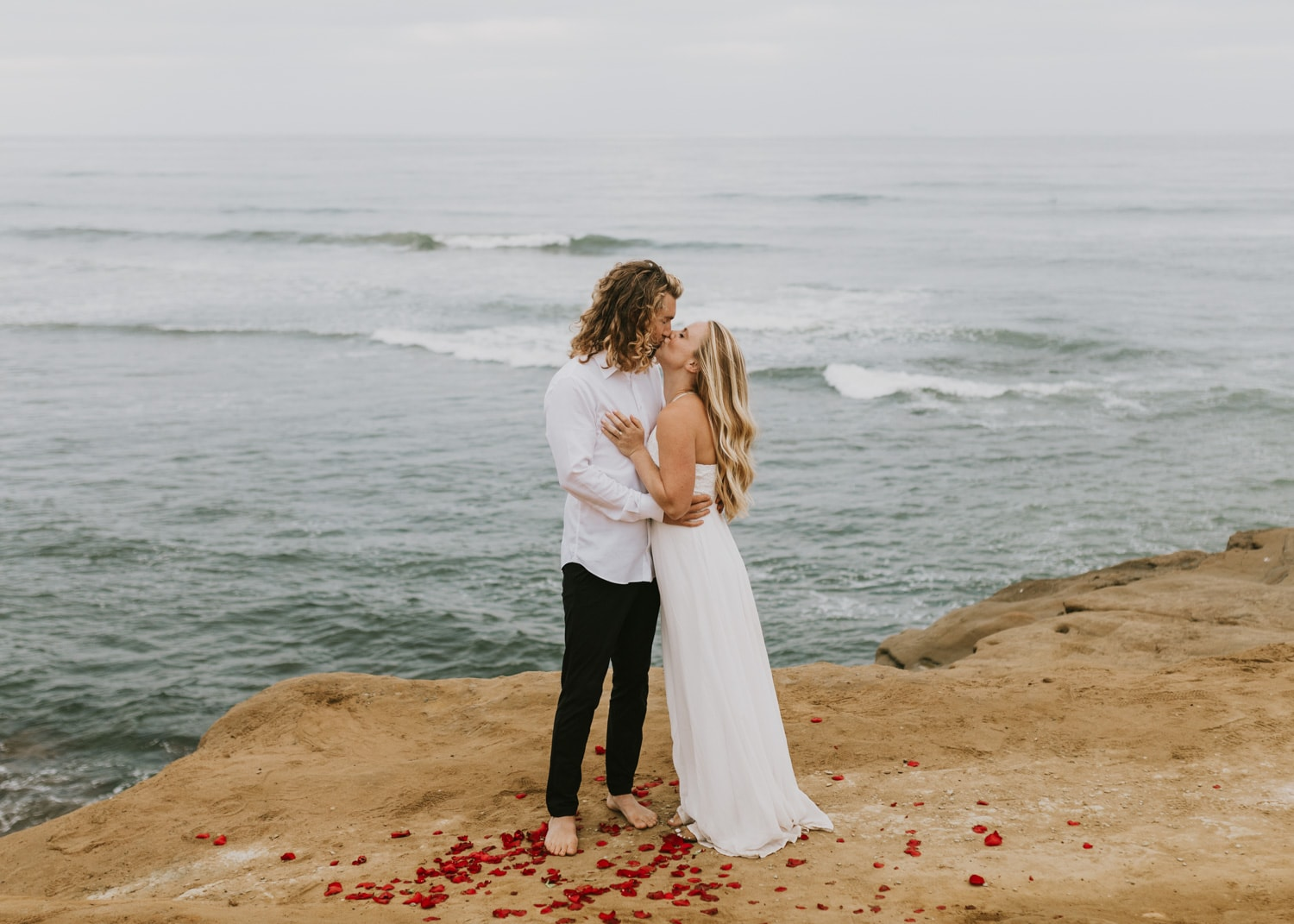 A bride and groom kissing at Sunset Cliffs in San Diego, California for their sunrise elopement, one of the best places to elope in California.