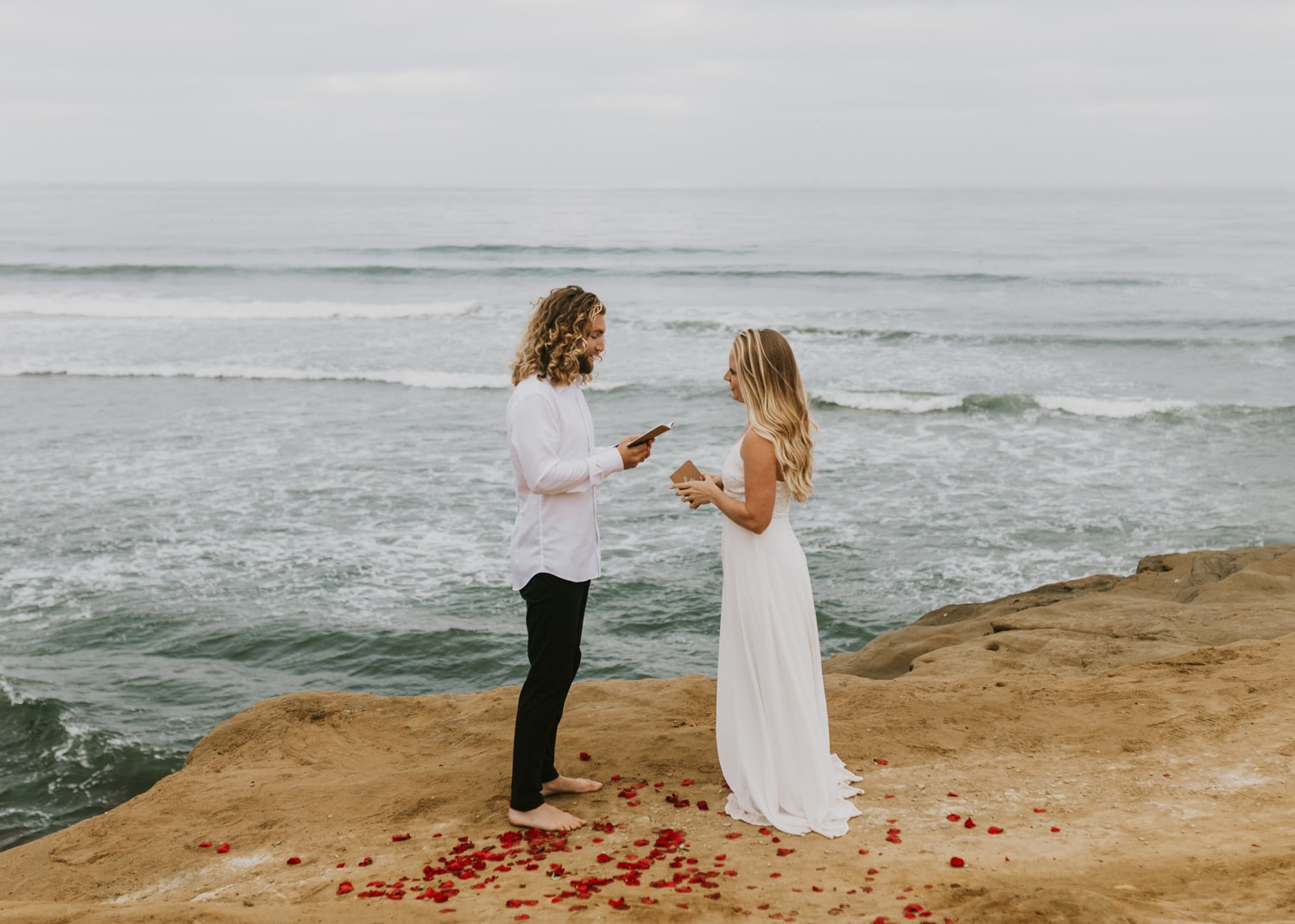 A bride and groom exchanging vows at Sunset Cliffs Natural Park in San Diego, California during their sunrise elopement.