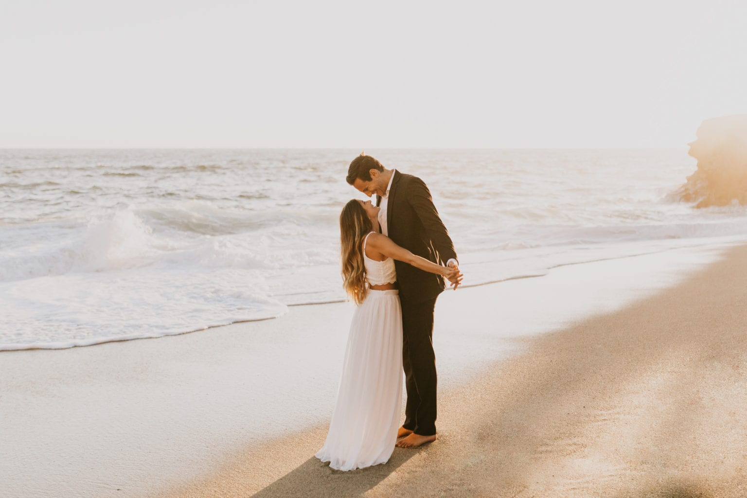 A couple having a sunset elopement at the beach during golden hour, captured by a California elopement photographer.