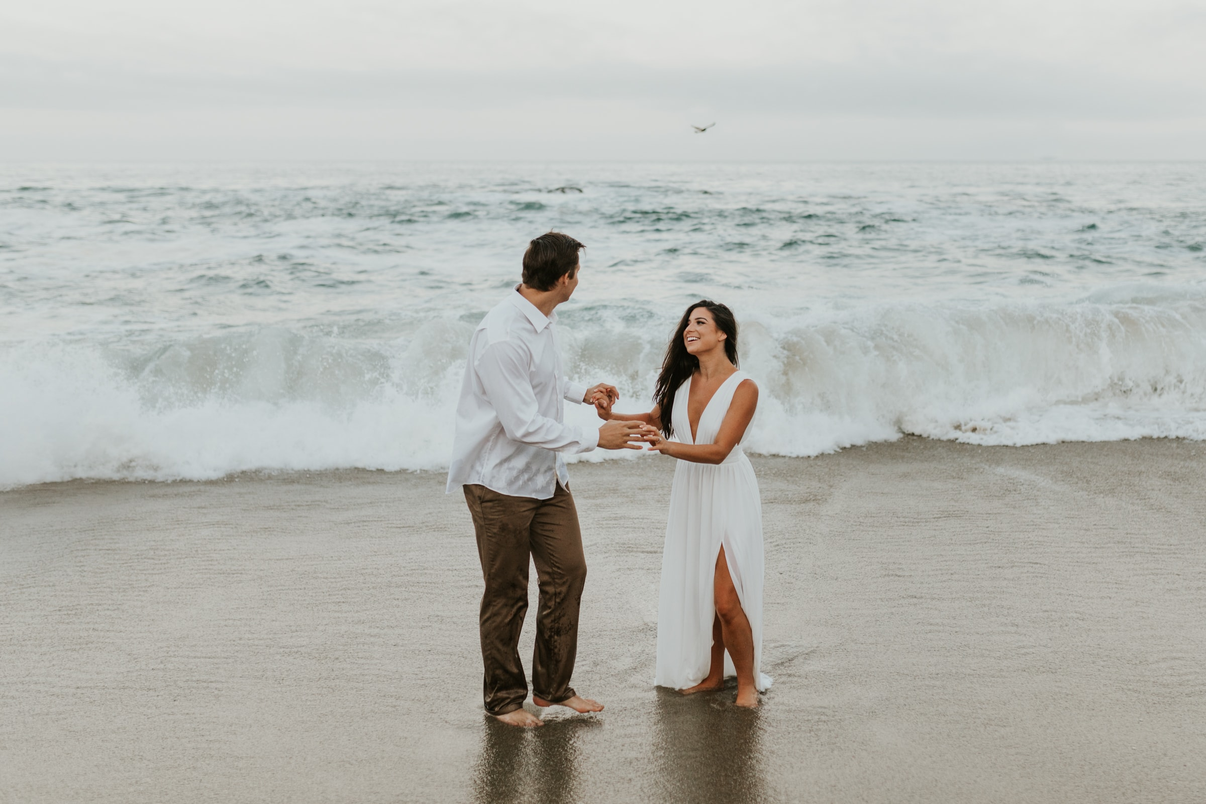 A couple playing on the beach during their sunset elopement.