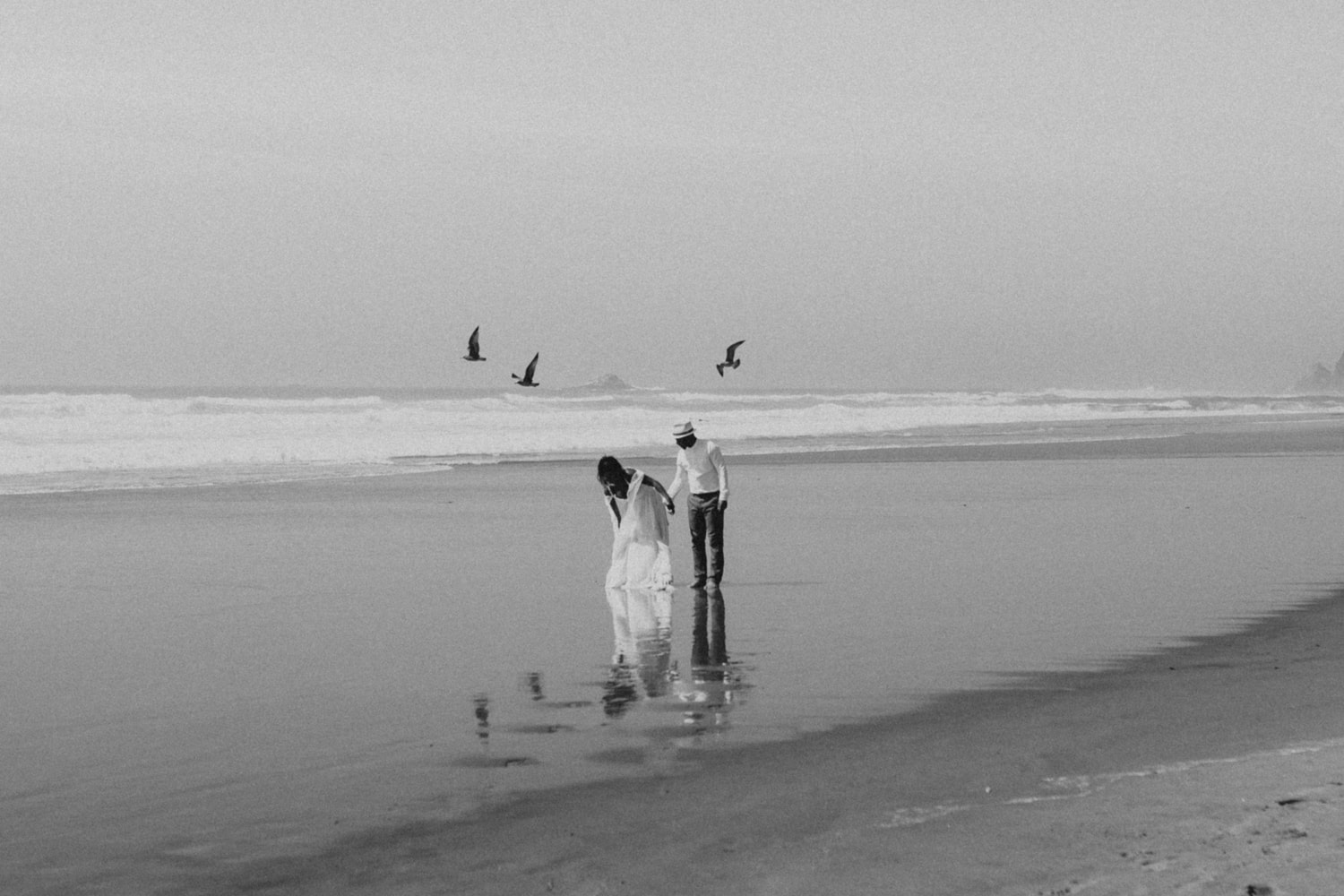 A bride and groom walking on the beach with birds on their wedding day.