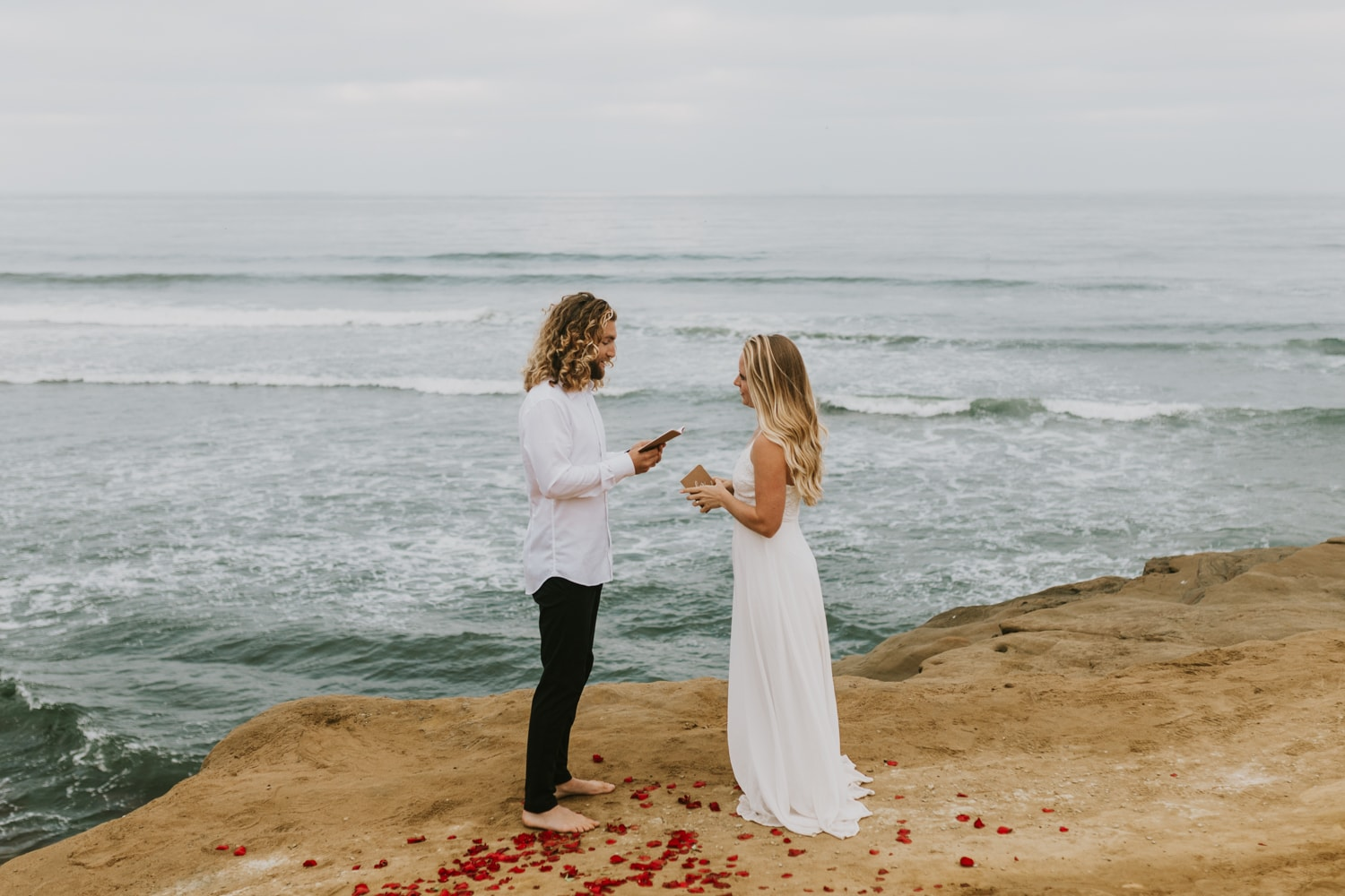 A bride and groom exchanging vows at Sunset Cliffs in California for their California elopement.