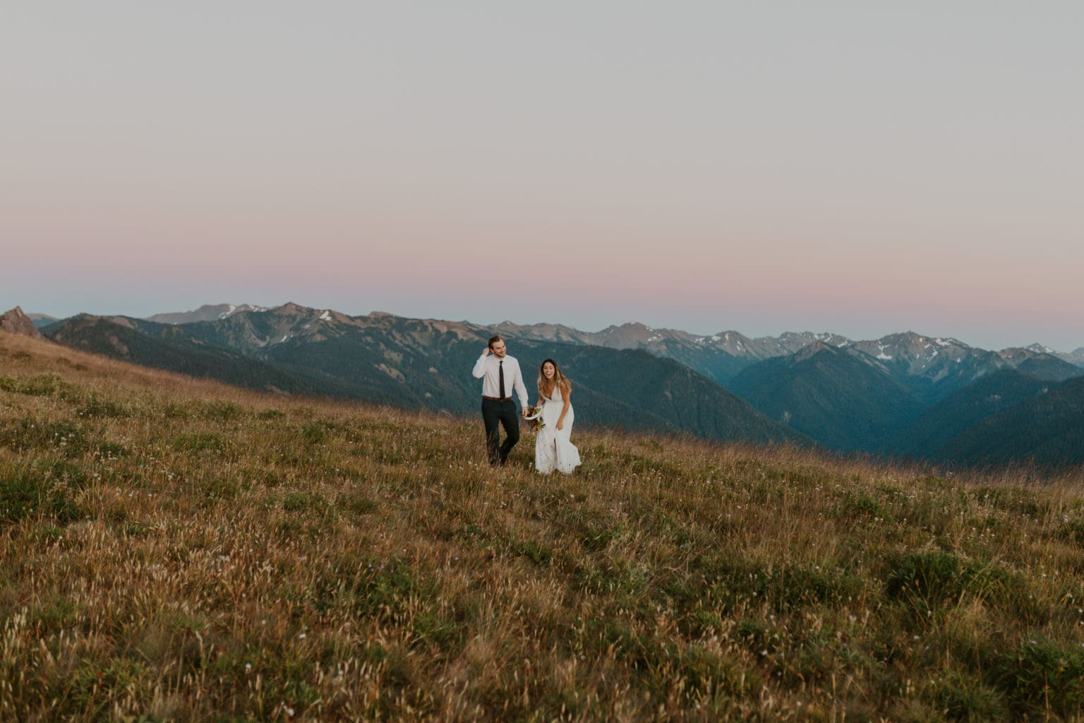 A bride and groom playing in the grass on their elopement day, taken by California elopement photographer, Brianna Parks.