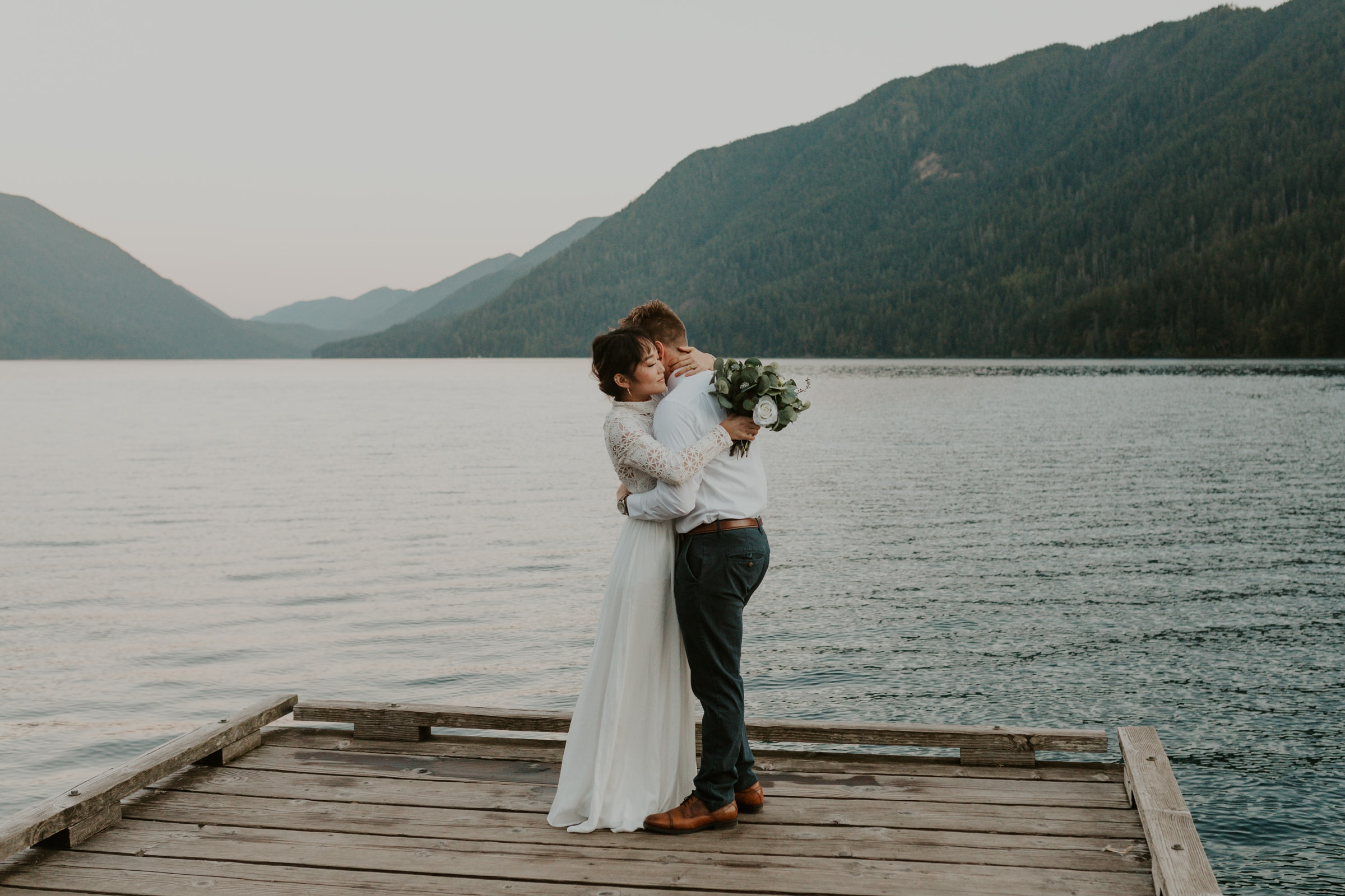 A couple hugging on their elopement day next to a lake in California.