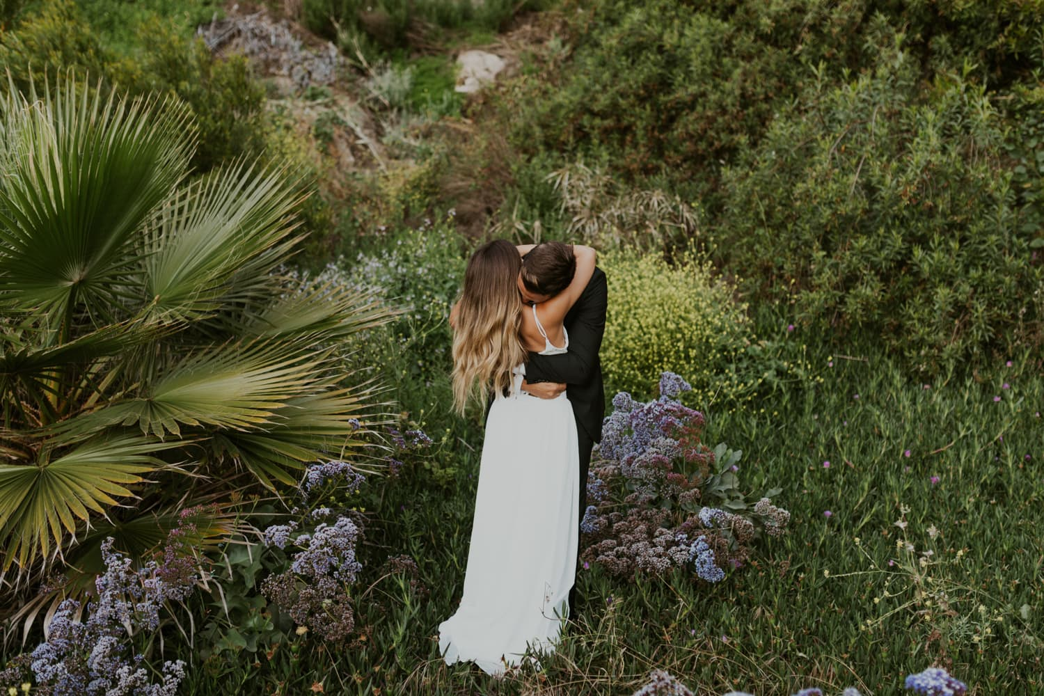A bride and groom hugging on a beach in California for their elopement.