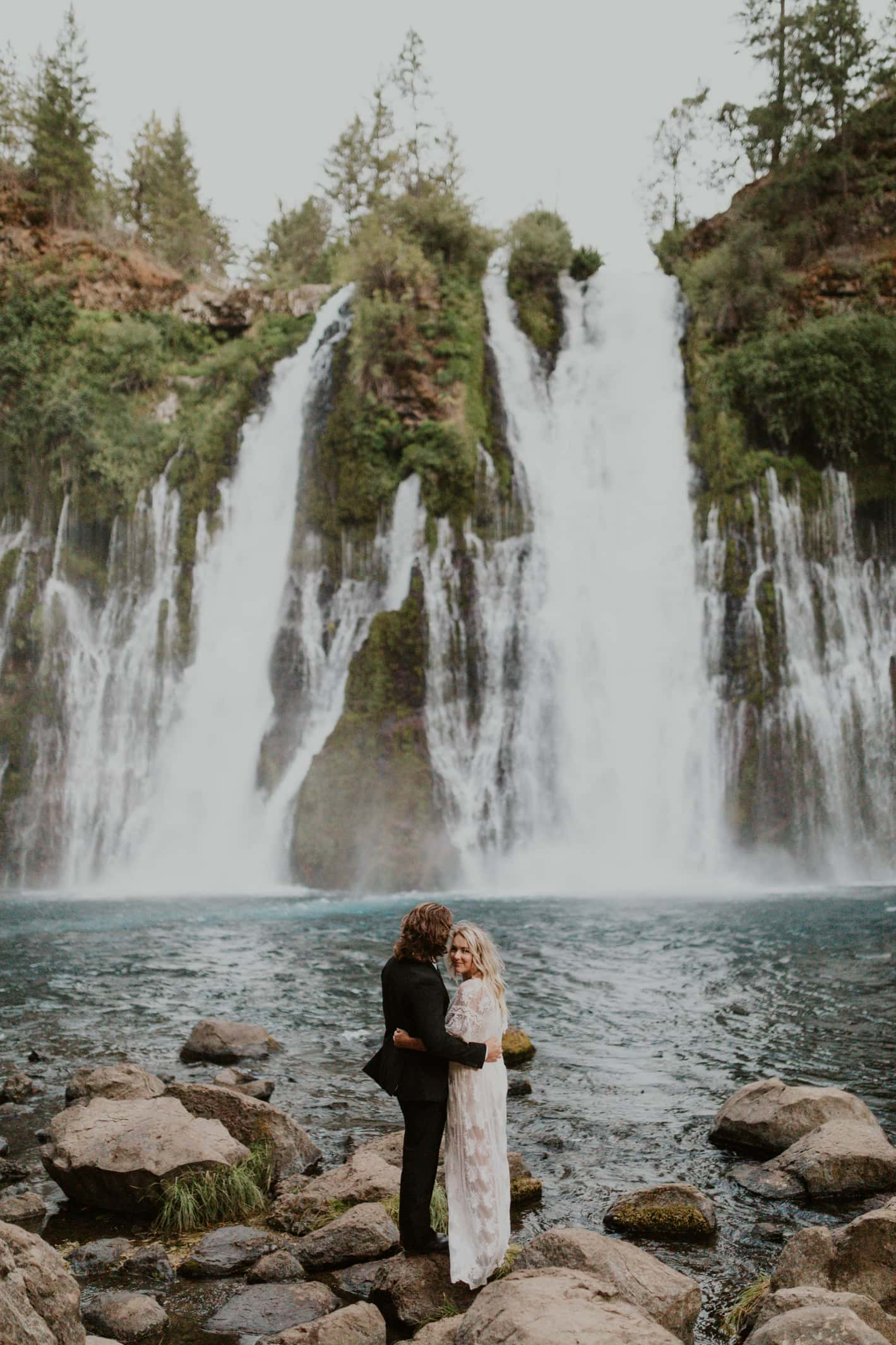A bride and groom at Burney Falls on their elopement day in California.