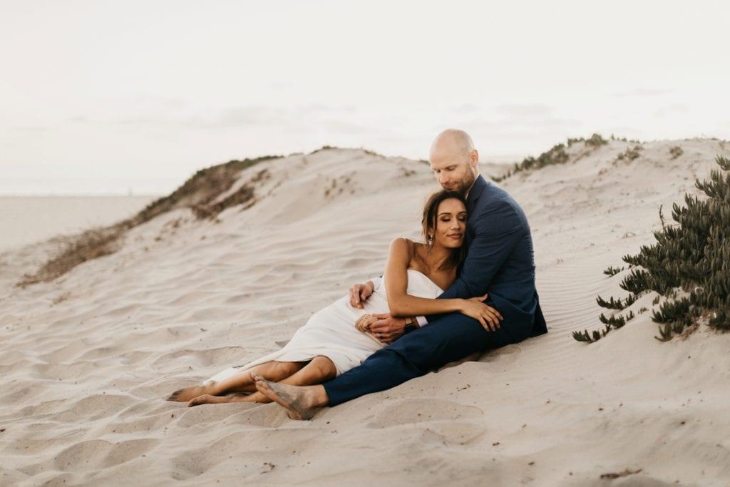 A bride and groom hugging on Coronado Beach, a beach venue in San Diego.