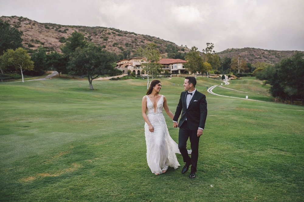 A couple walking on the Vista Valley Country Club, an outdoor wedding venue in San Diego.