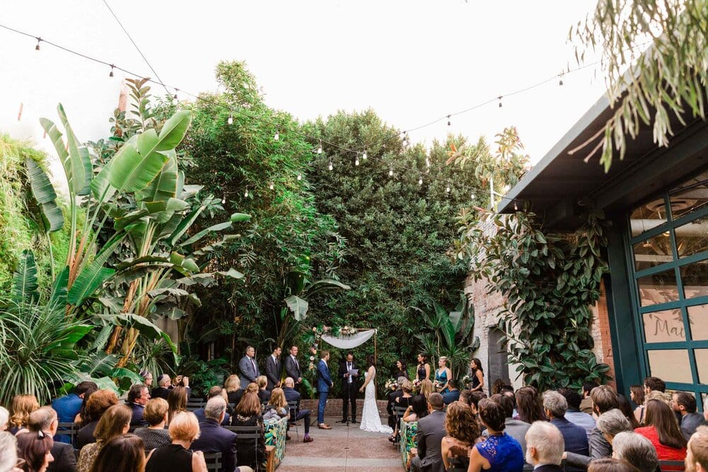 A bride and groom exchanging vows at Millwick, an outdoor wedding venue in Los Angeles.