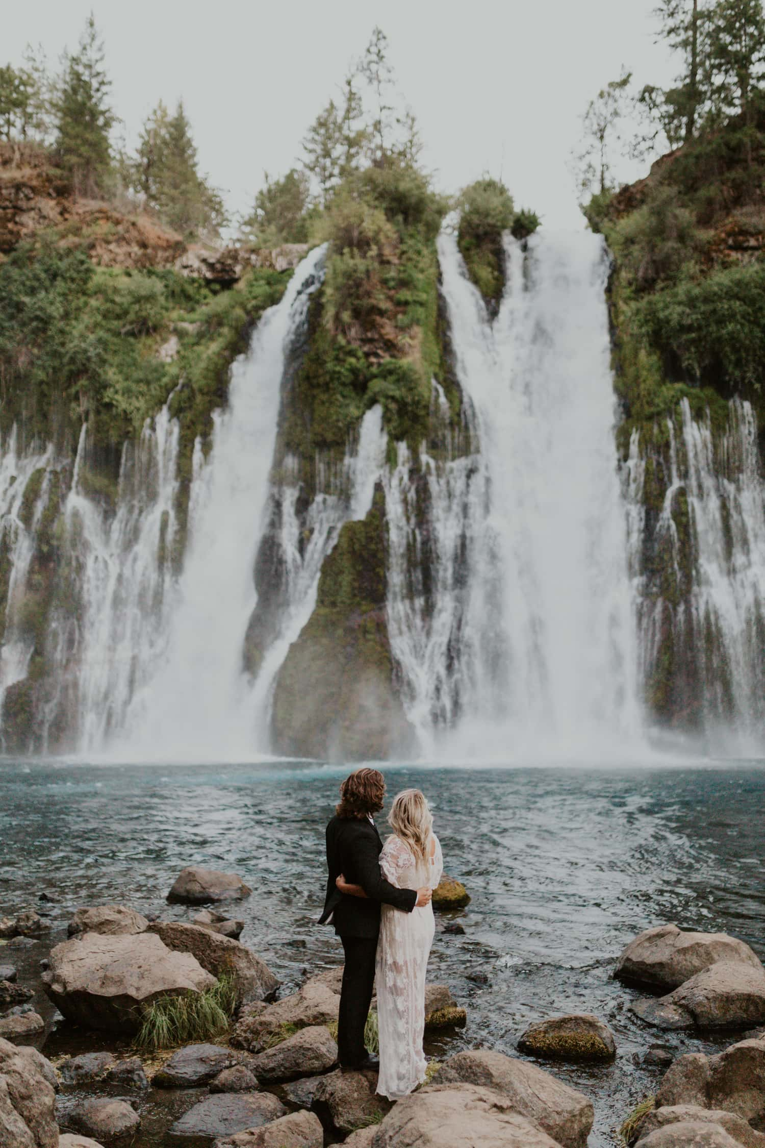 A couple having a waterfall wedding at Burney Falls, a waterfall in Northern California.