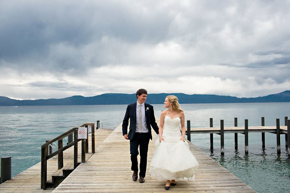 A couple walking on Sugar Pine Point State Park Pier​ on their wedding day at an outdoor wedding venue in Lake Tahoe.
