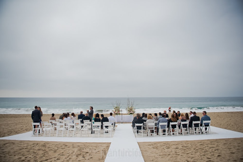 Guests at a wedding on the beach at The Sunset Restaurant, an outdoor wedding venue.