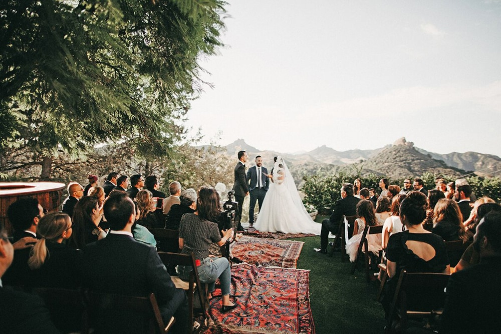 A couple exchanging vows at Le' Sangreal, an outdoor wedding venue in Malibu.