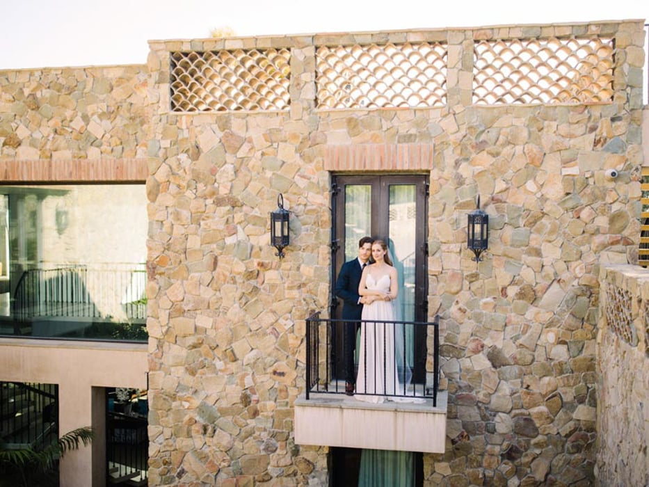A couple hugging on the balcony of Casa di Pietra, an indoor wedding venue in Malibu.