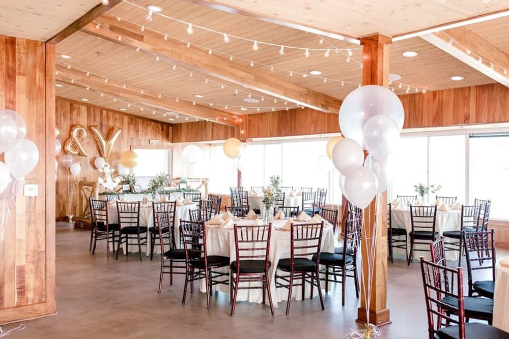 A reception setup with chairs and tables at Duke's Malibu, an indoor Malibu wedding venue.