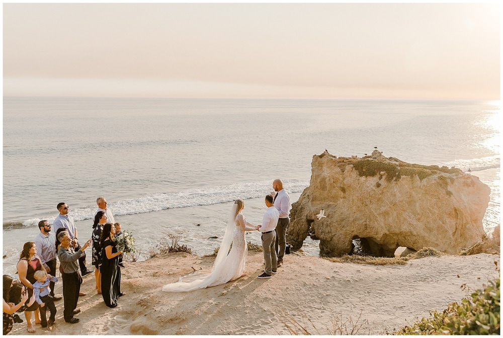 A couple exchanging vows on El Matador Beach, an outdoor wedding venue in Malibu.