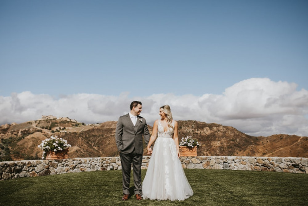 A couple holding hands at Cielo Farms, an outdoor wedding venue in Malibu.