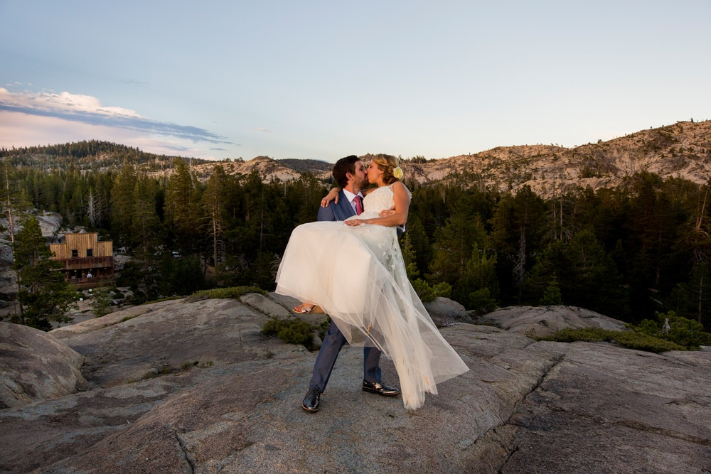 A couple kissing on top of a rock at The Hideout, a Sacramento wedding venue.