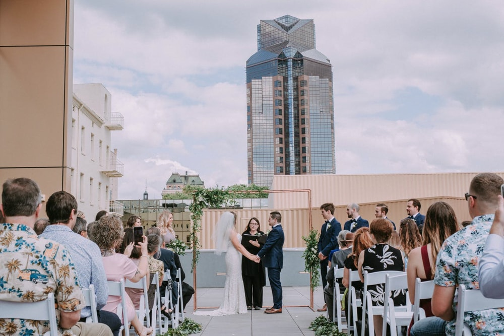 A bride and groom getting married at the top of the Kimpton Hotel, an outdoor wedding venue in Sacramento.