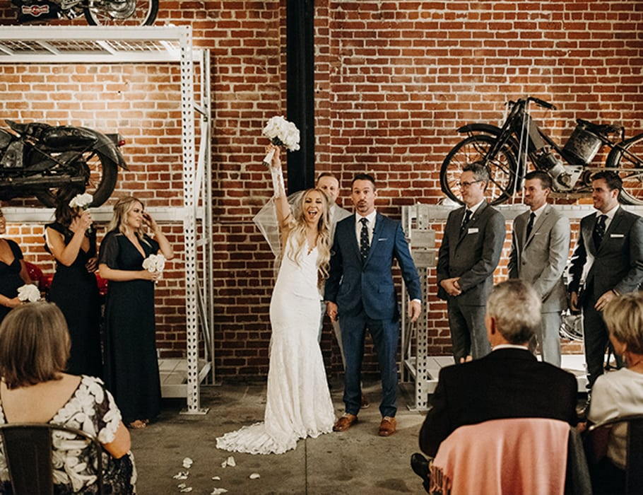 A bride and groom cheering in the Vintage Monkey, an indoor wedding venue in Sacramento.