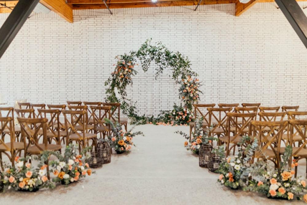 A floral wedding arch against a white white in BLOC, a Sacramento wedding venue.