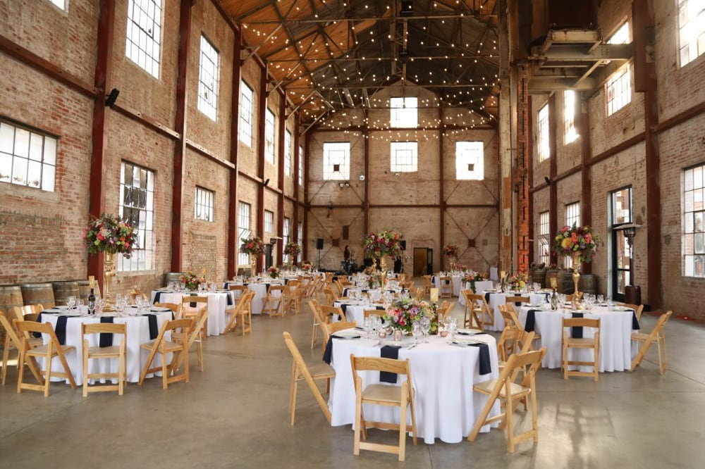 A ceremony setup with chairs and tables inside the Old Sugar Mill, a wedding venue in Sacramento.