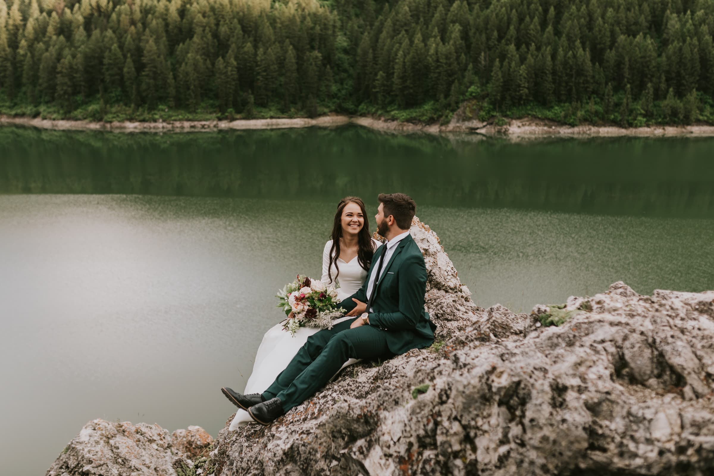 A bride and groom sitting on a rock in the forest on their wedding day.
