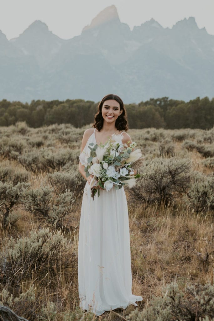 A bride wearing a forest wedding dress from ASOS while smiling at the camera.