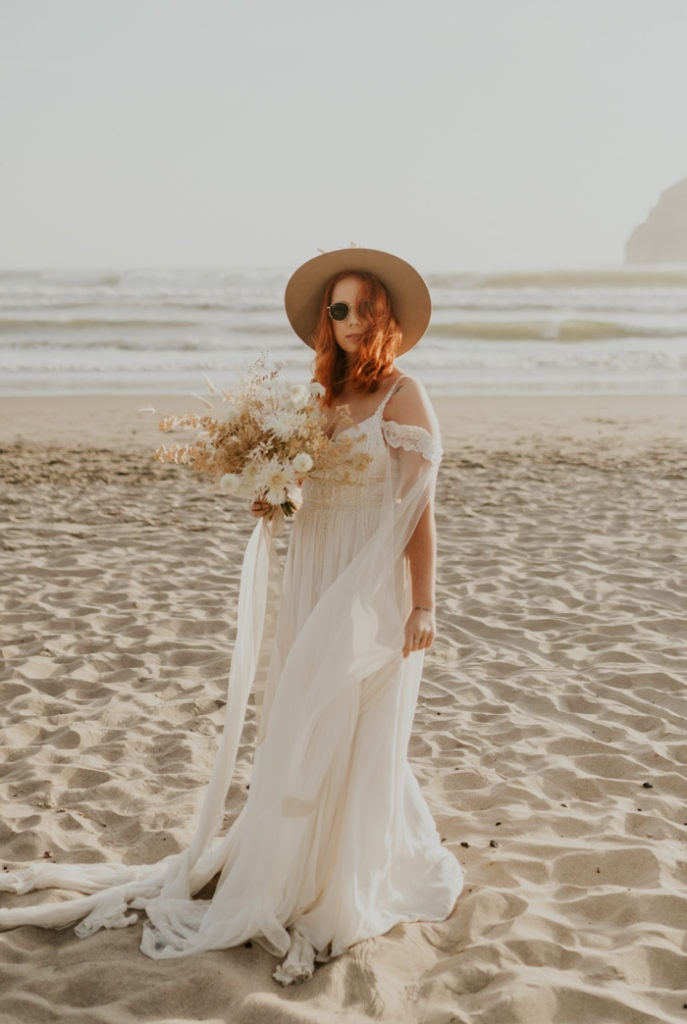 A model wearing a forest wedding dress on the beach from Daci Gowns.