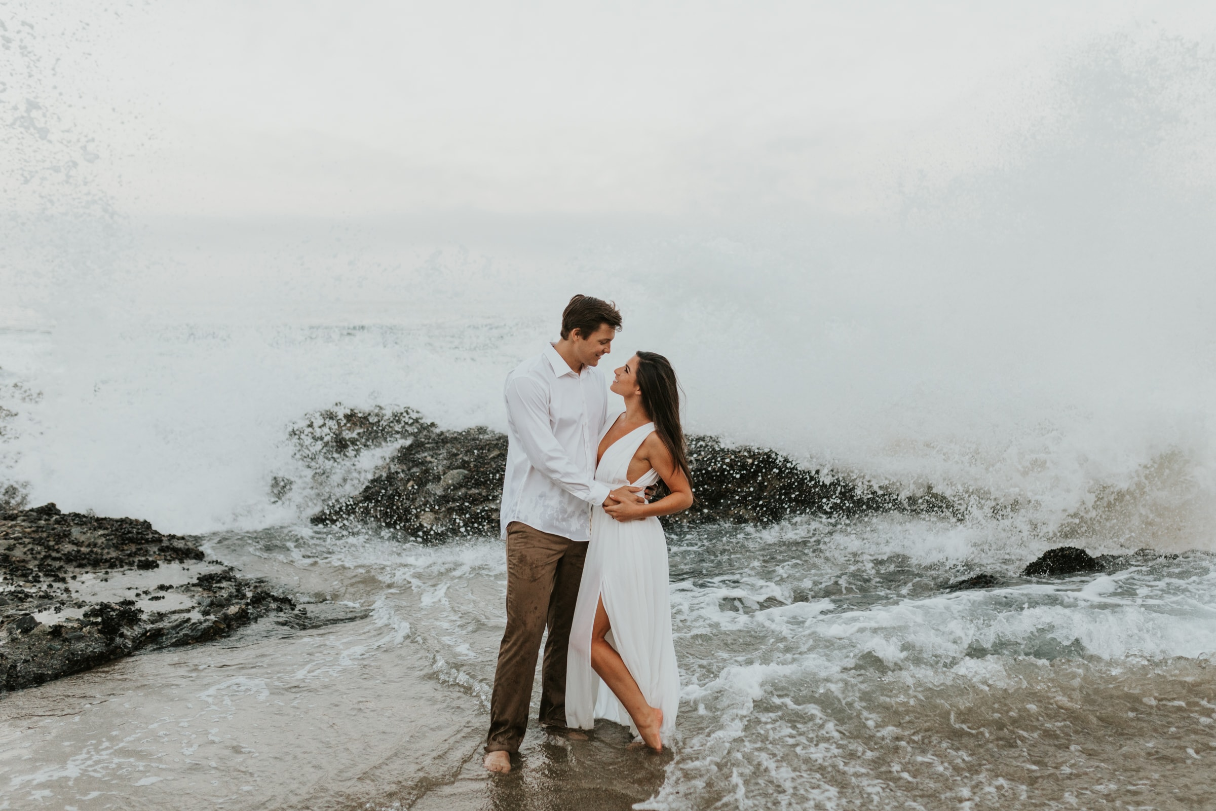 A couple looking at each other as a wave crashes behind them in Hawaii.