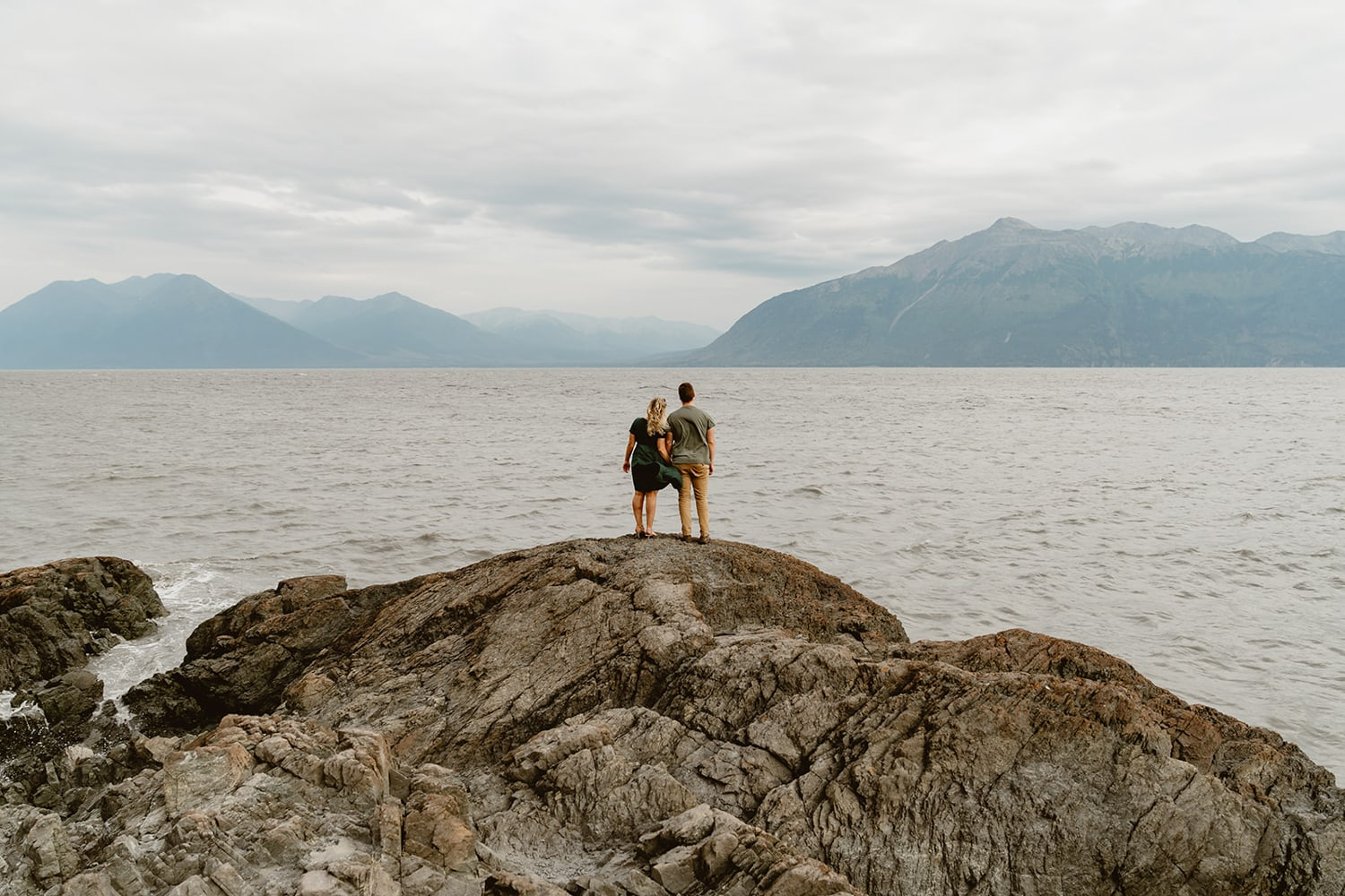 A couple standing next to the water in Alaska.