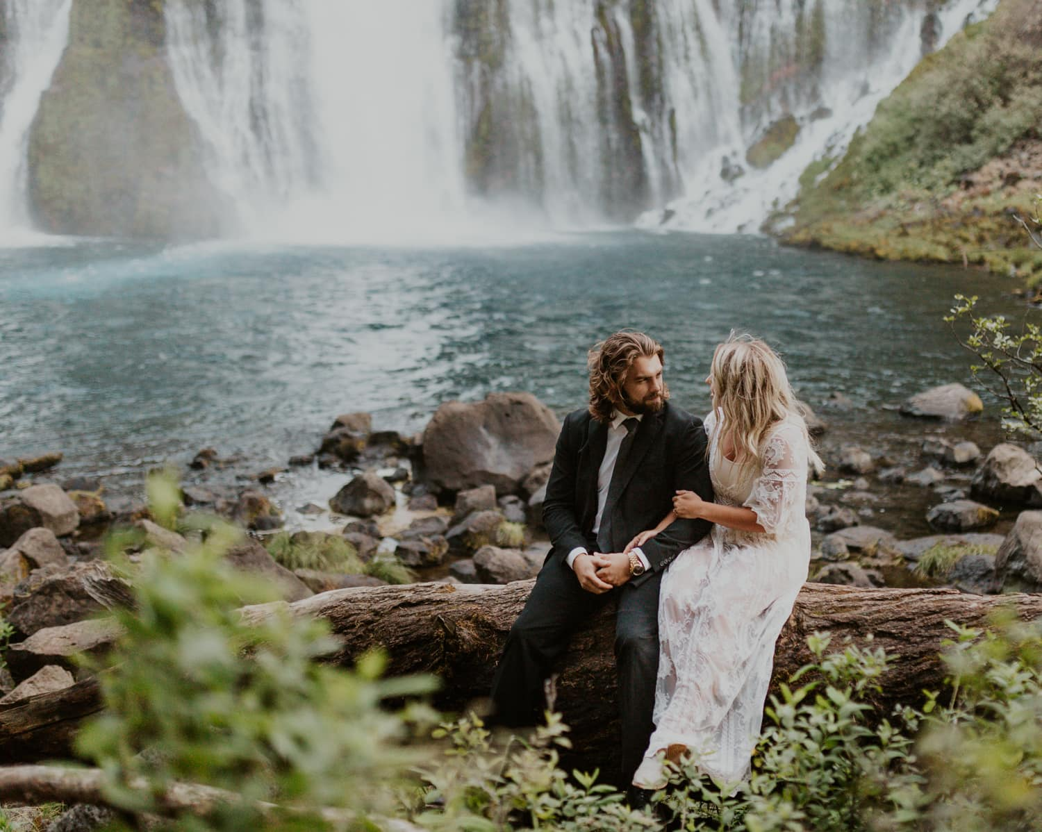 A bride and groom sitting at the base of Burney Falls on their wedding day.
