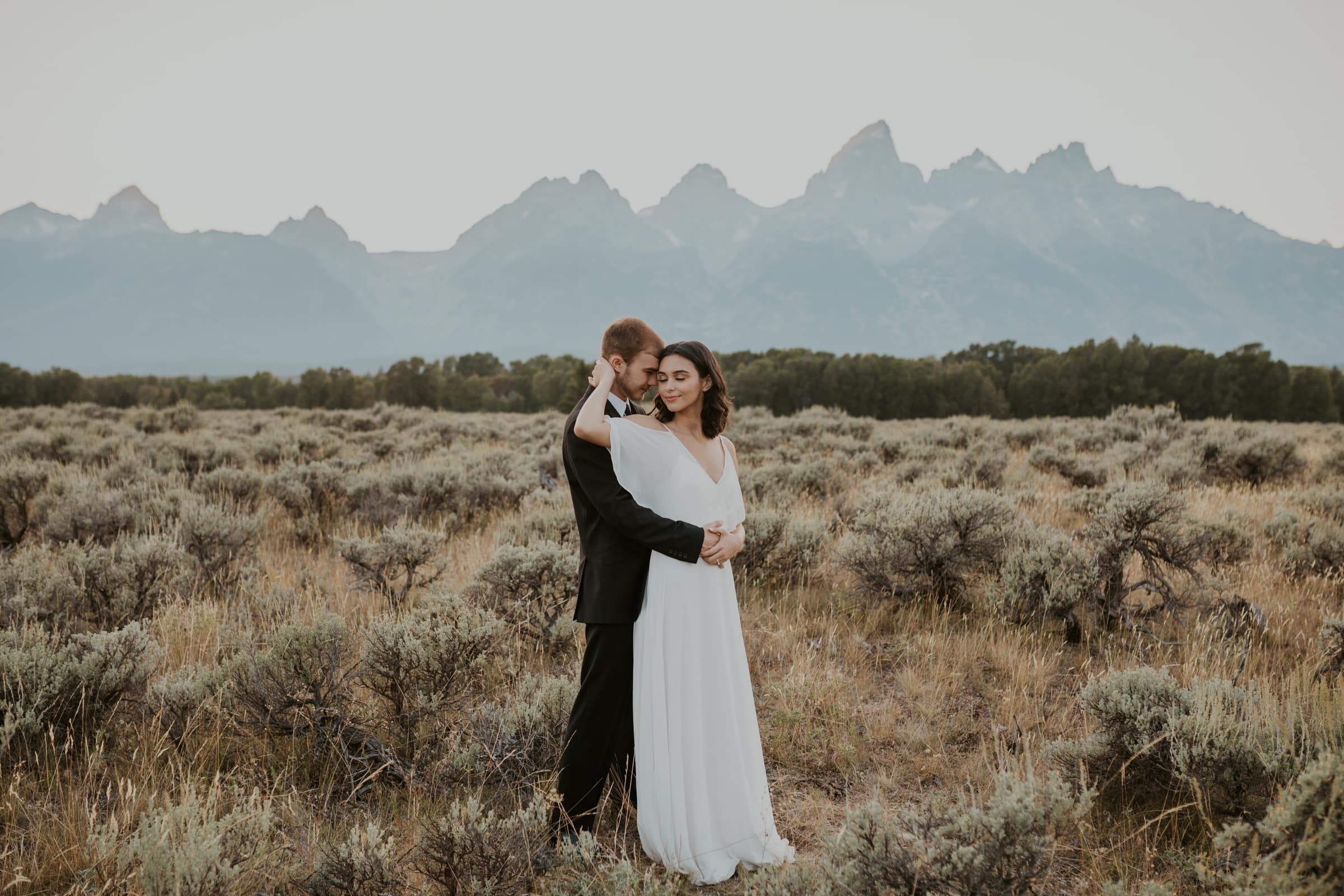 A bride and groom hugging in Grand Teton National Park.