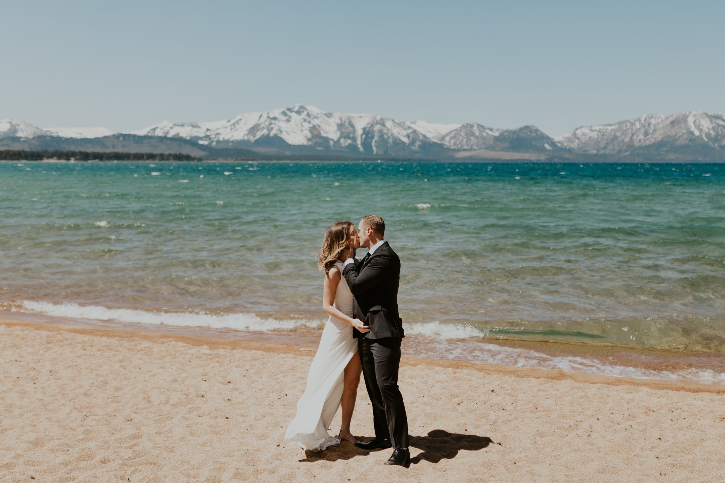 A couple kissing on the shoreline of Lake Tahoe for their elopement.