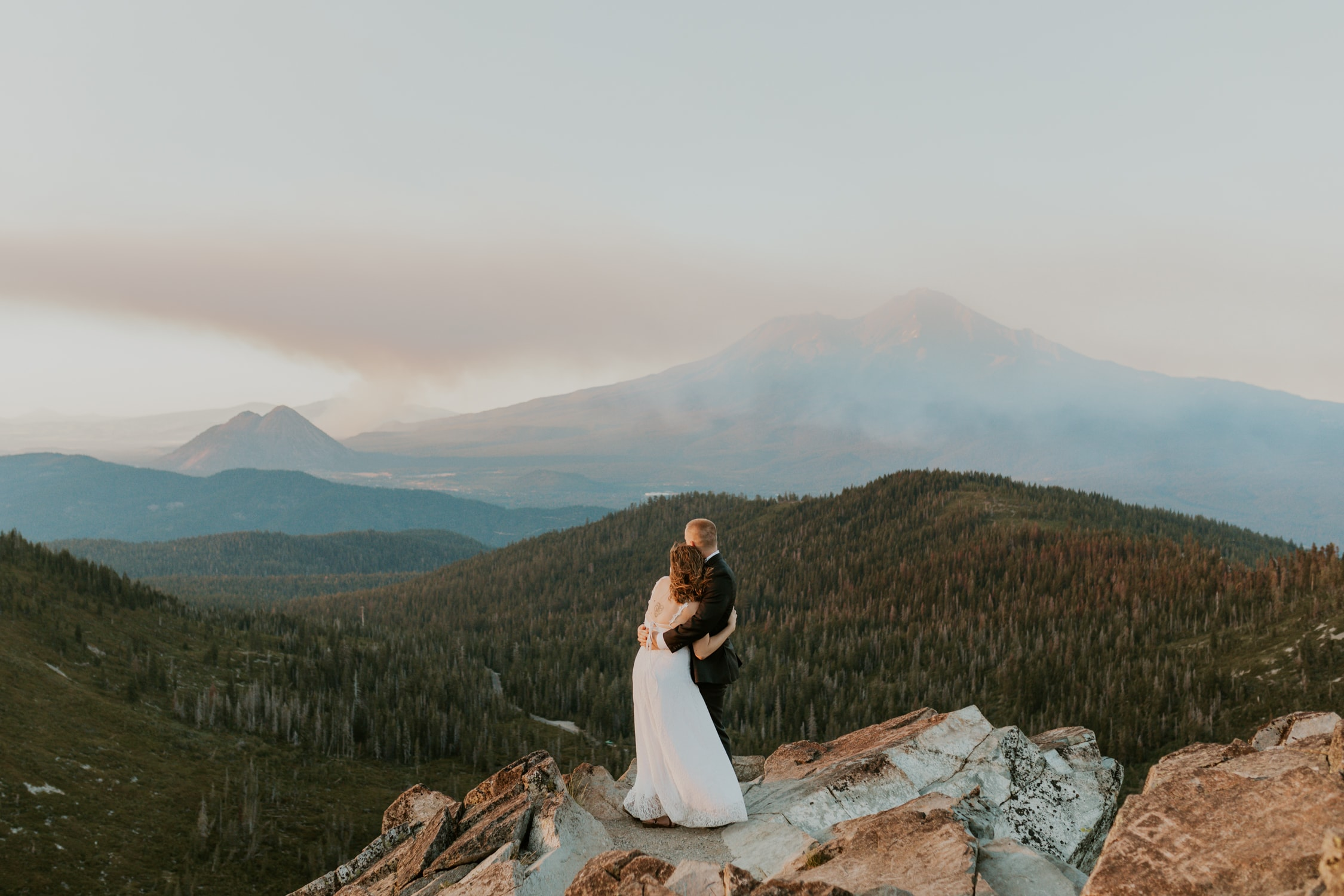A couple hugging each other by a mountain on their elopement day.