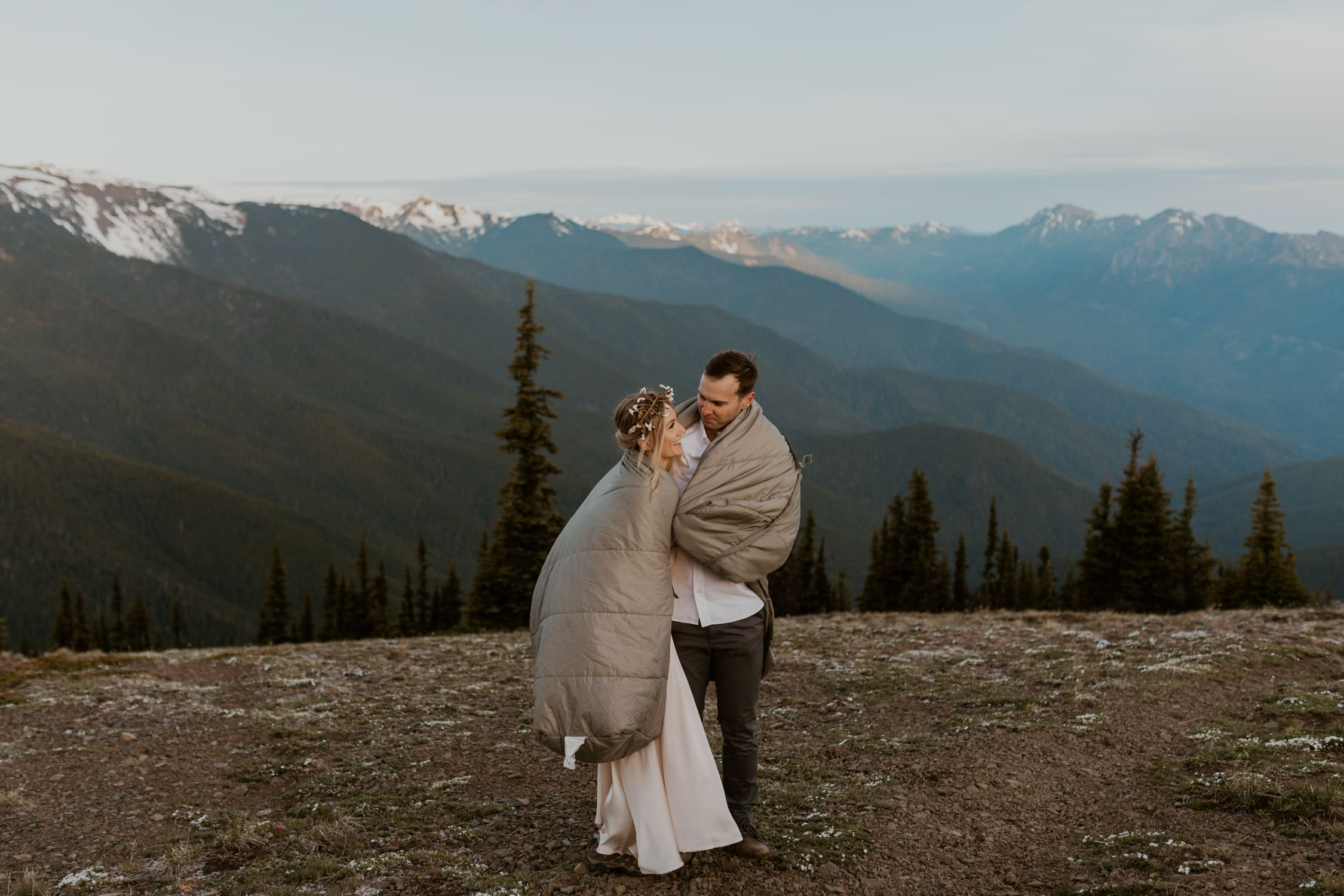 A couple wrapped in a blanket and laughing on a mountain.