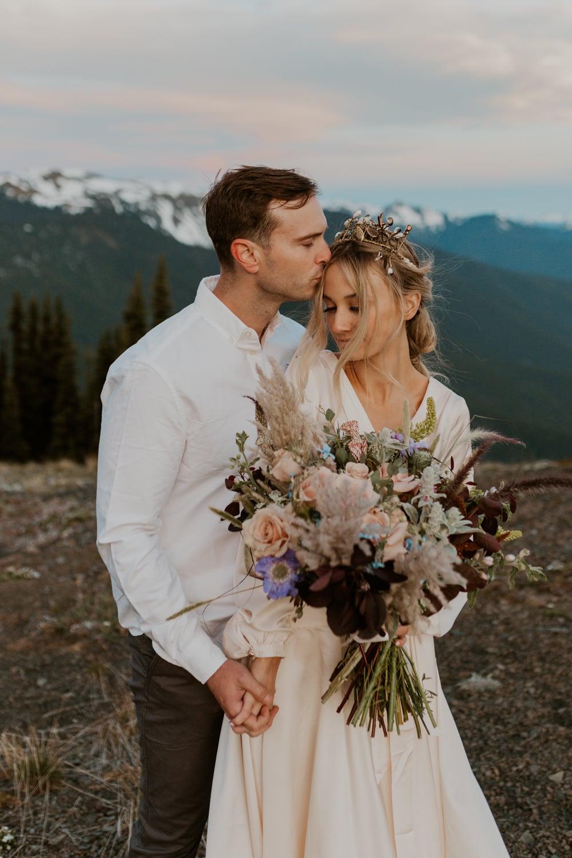 A groom kissing his bride's forehead on Hurricane Ridge on their wedding day.