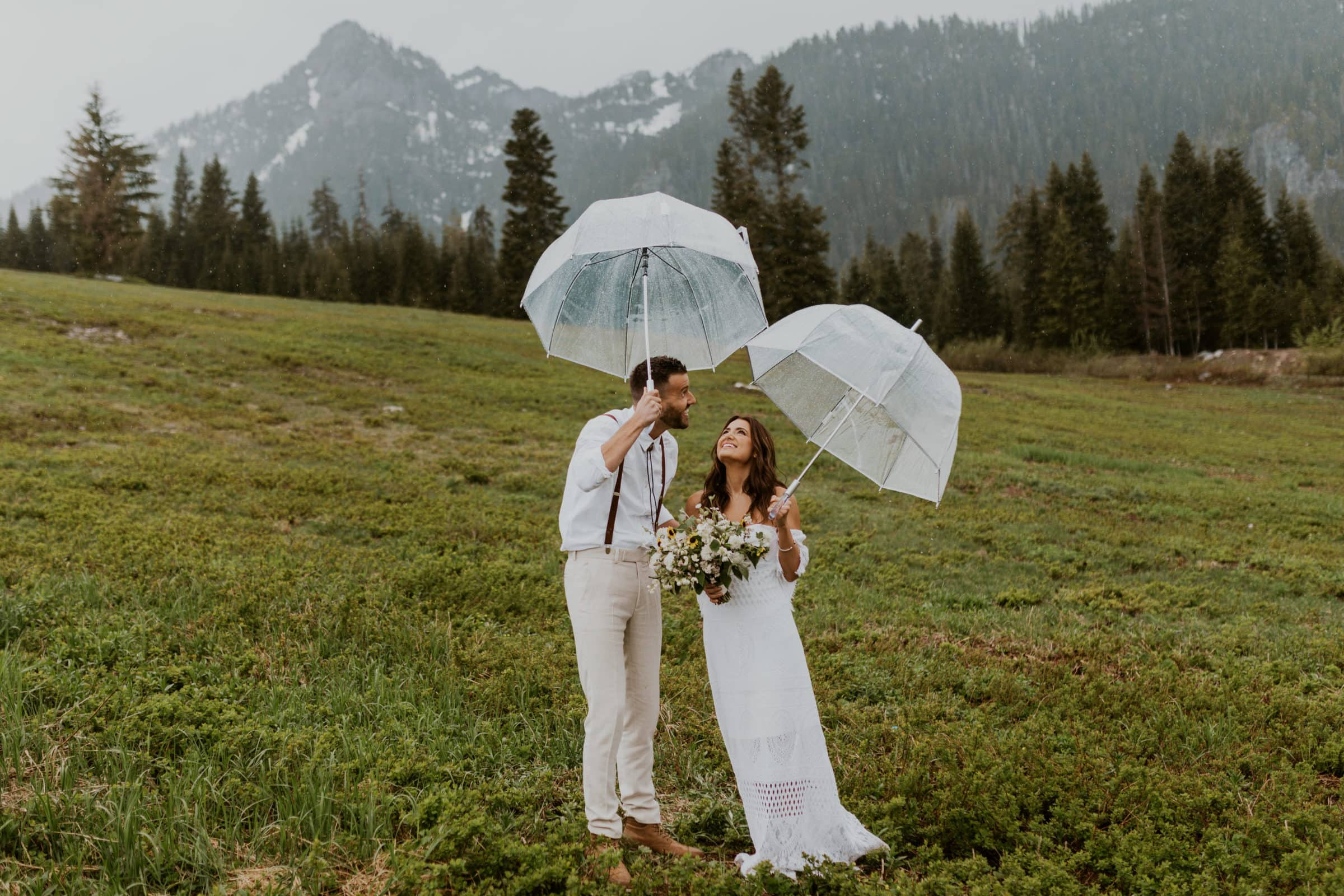 A bride and groom holding clear umbrellas and smiling with mountains in the back in Washington State.
