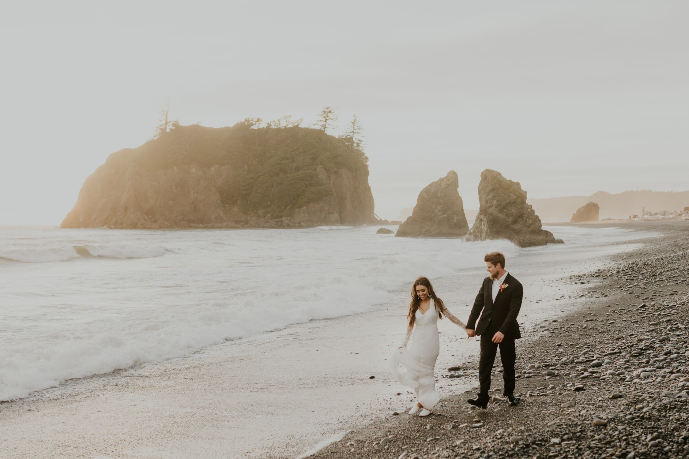 A couple walking across Ruby Beach for their elopement.