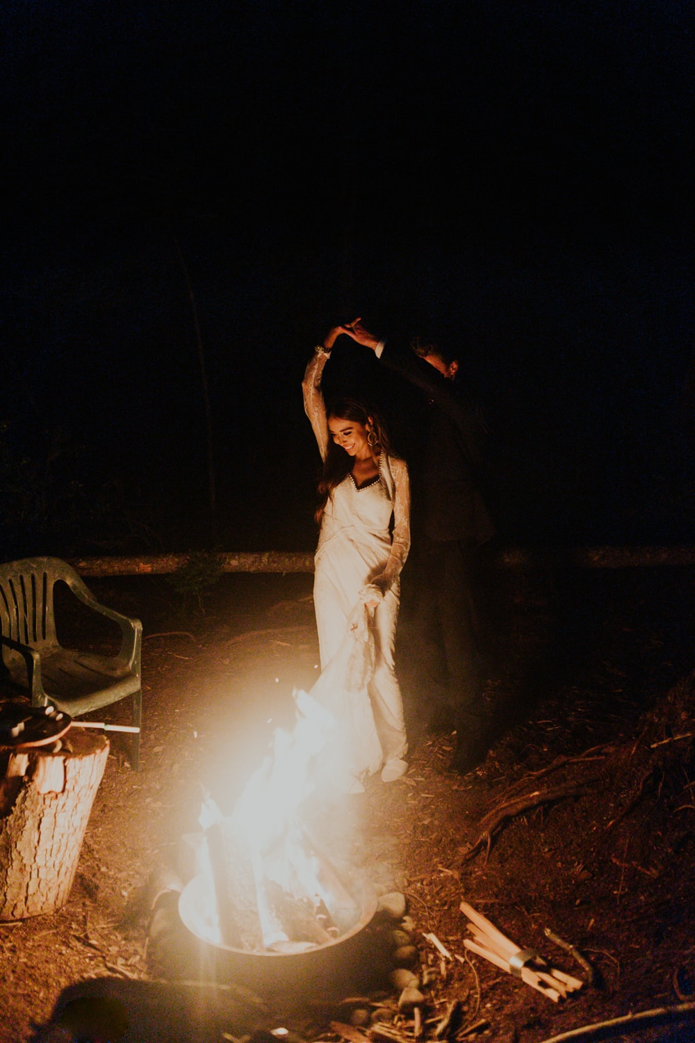 A couple dancing next to a campfire on their elopement day.