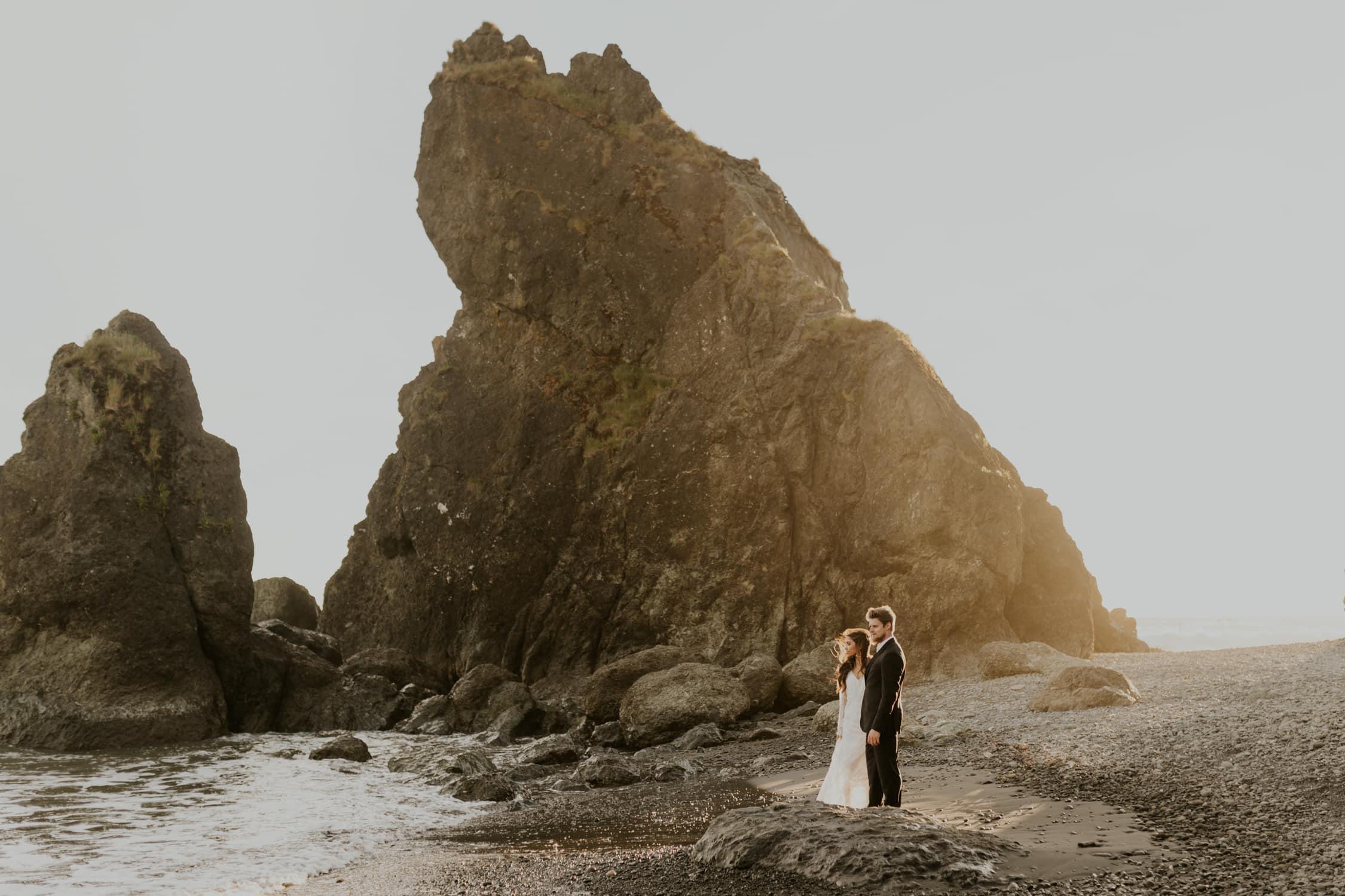 A couple looking at the ocean on Ruby Beach on their elopement day.