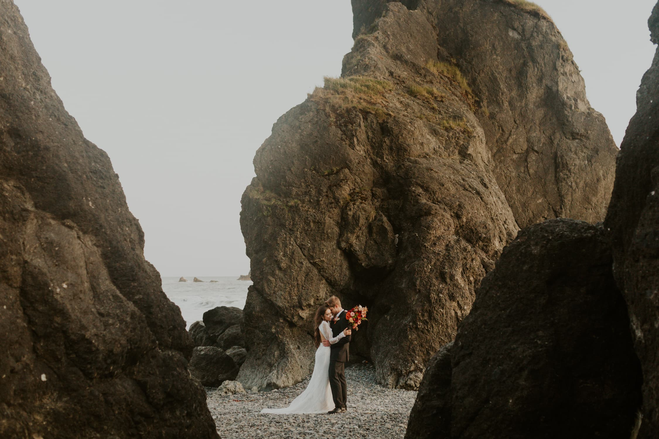 A couple hugging each other on their elopement day on Ruby Beach in Washington State.