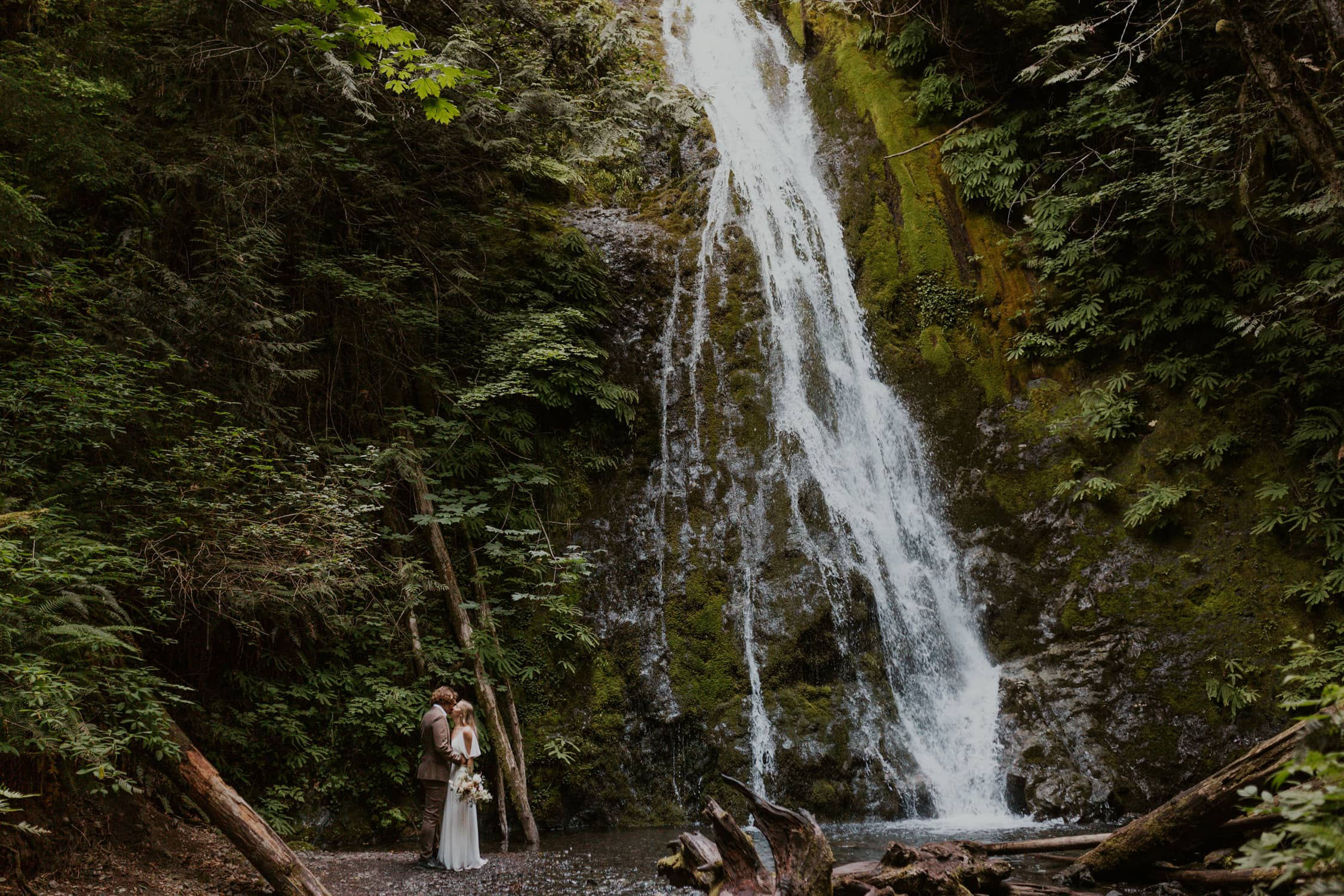 A bride and groom kissing on their elopement day next to a waterfall in Washington State.