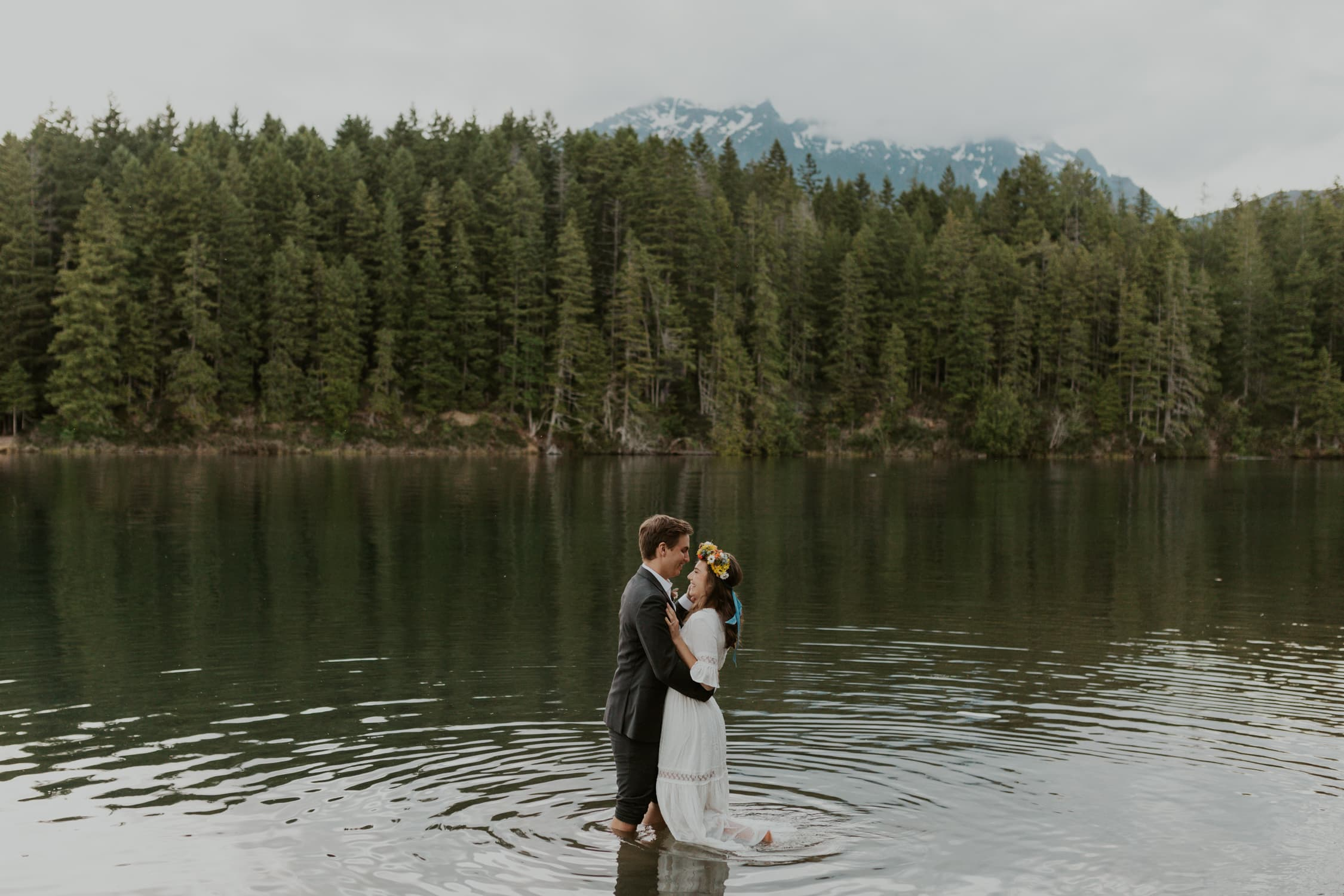 A couple laughing and playing in the water of Lake Cushman in Olympic National Park in Washington State.