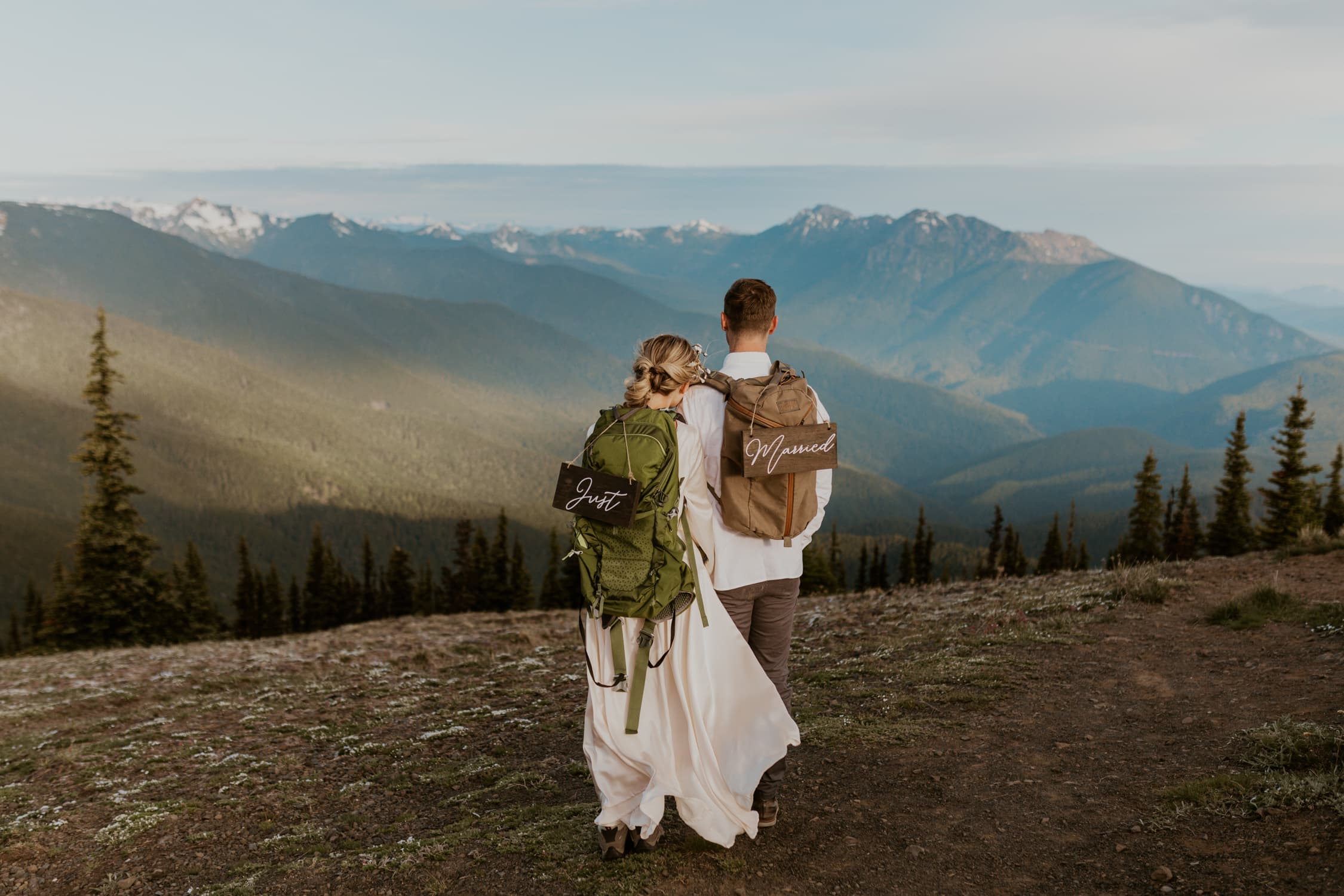 A bride and groom holding each other and looking at Hurricane Ridge with just married signs on their backpacks.
